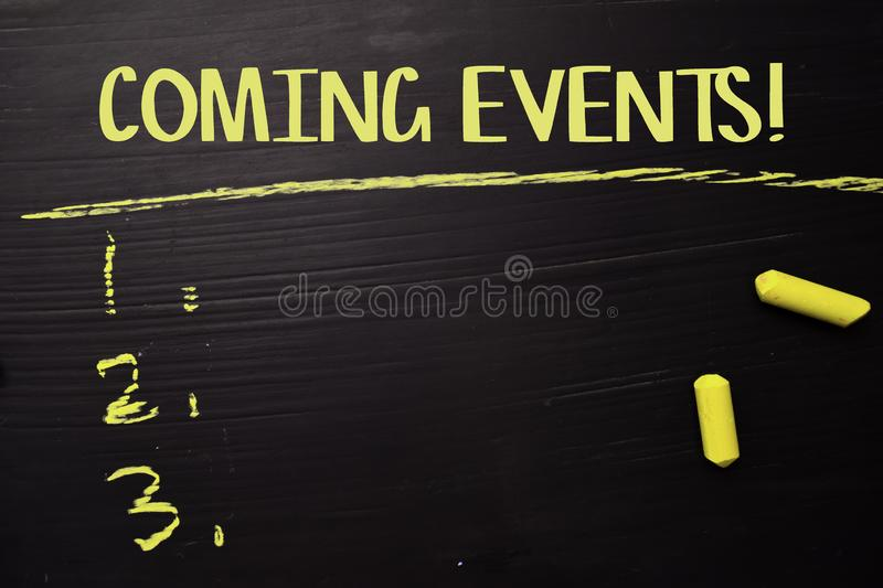 Coming Events! written with color chalk. Supported by an additional services. Blackboard concept royalty free stock photo