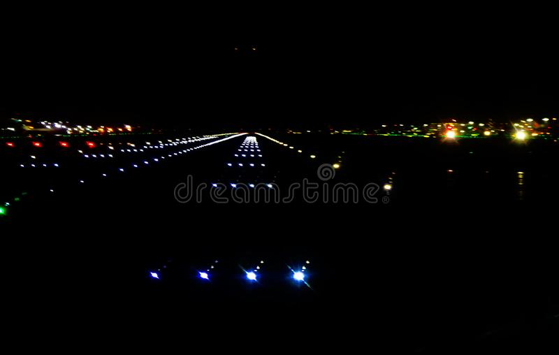 Coming in for a landing - Abstract airport runnway in the dark on a wet night backgound royalty free stock photo