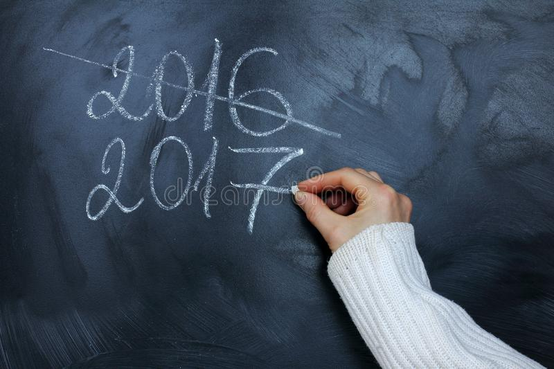 Coming new 2017. Hand in a warm sweater chalk writes a new date on the blackboard stock photography