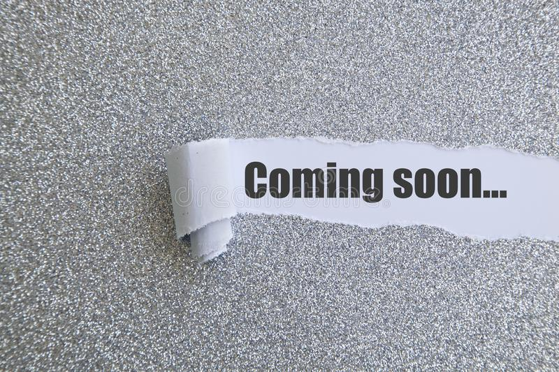 Coming soon... Coming soon word written under torn paper concept royalty free stock photo
