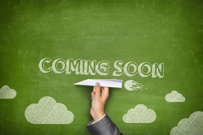Coming soon concept. On green blackboard with businessman hand holding paper plane stock images