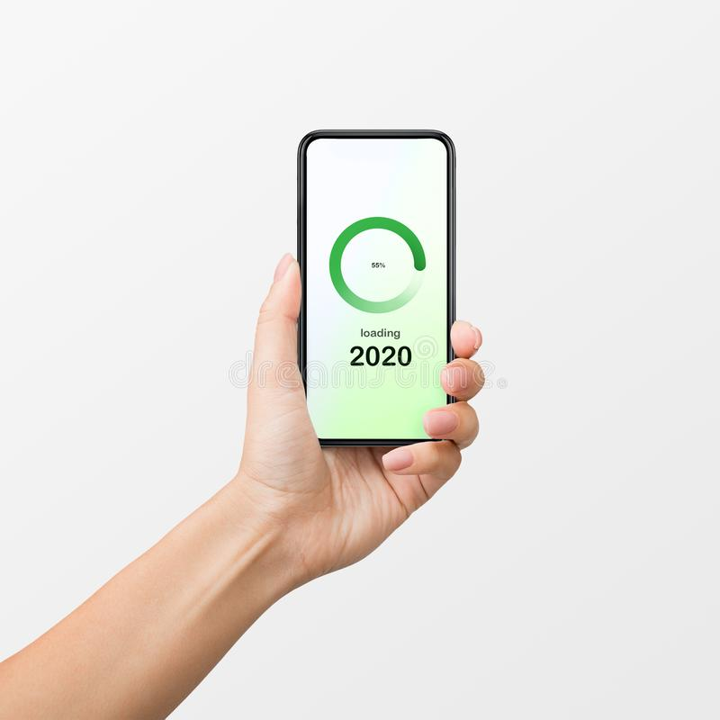 2020 coming soon concept. Woman`s hand holding smartphone with 2020 number loading on screen on white background. 2020 coming soon concept stock photos