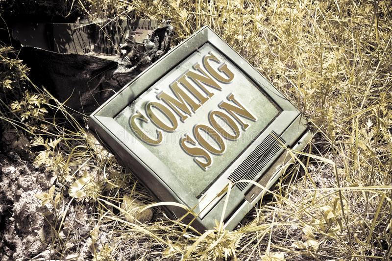 Coming soon concept written on an screen of an old CRT television - toned image.  royalty free stock photos