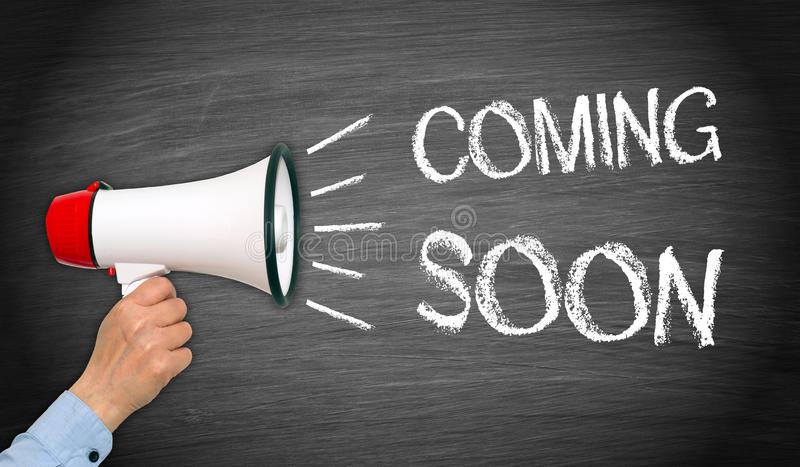 Coming soon - female hand with megaphone and text royalty free stock image