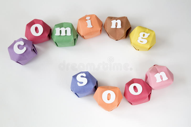 Coming soon. Sign on color paper ball background royalty free stock photo