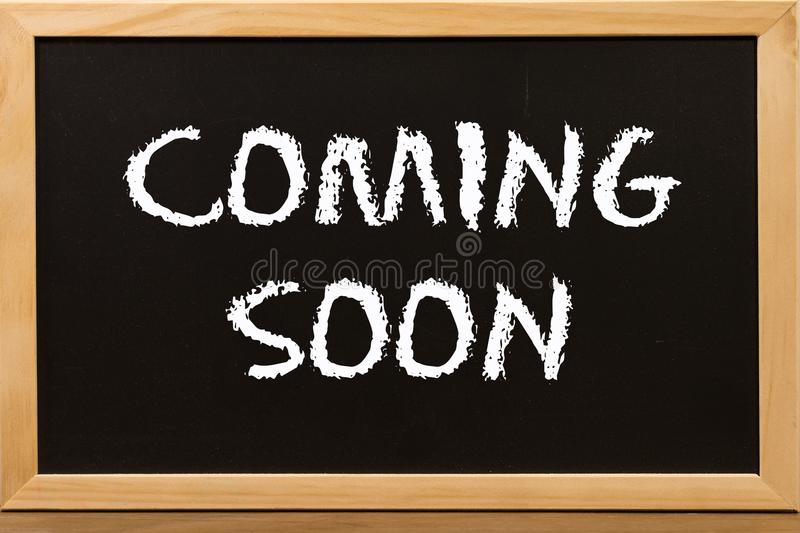 Coming soon write by white chalk on chalkboard. Concept background for business stock images