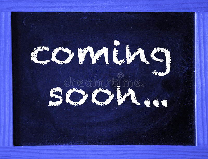 Coming Soon written on blue chalk board. The words Coming Soon written on blue chalk board royalty free stock photo