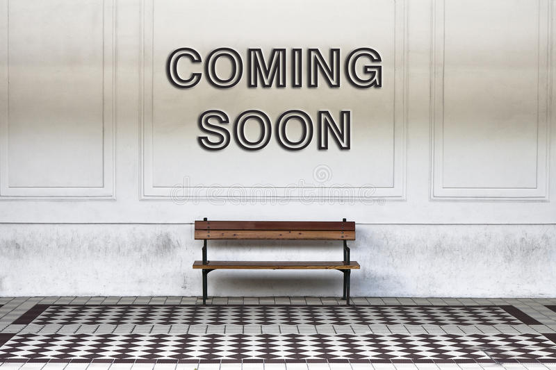 Coming soon written on a wall above a wooden bench - concept image royalty free stock image