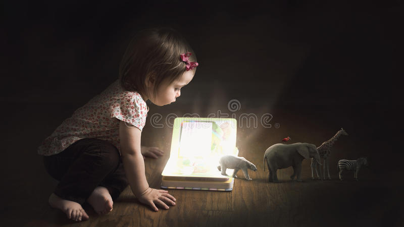 Coming to life. A child reads a book with animals walking off the page stock image