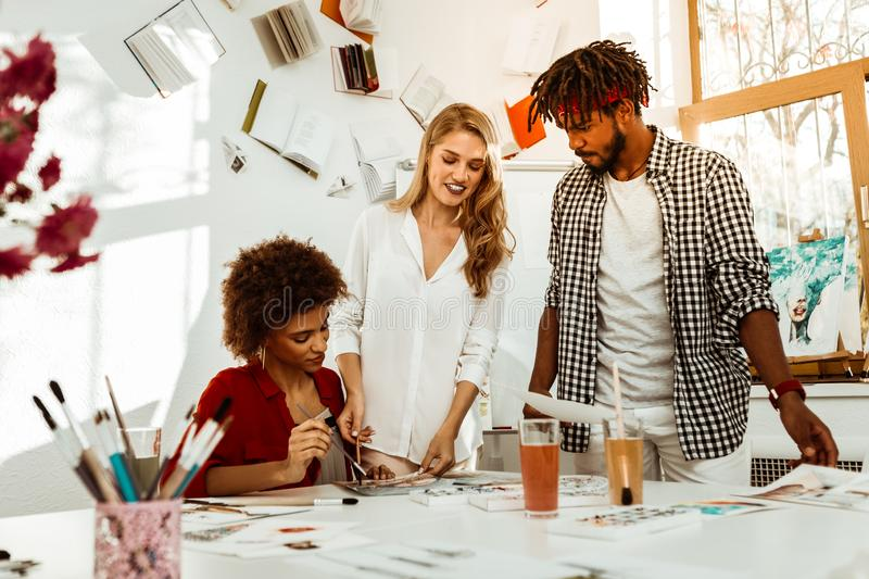 Bearded man with dreadlocks wearing squared shirt coming to teacher. Coming to teacher. Bearded men with dreadlocks wearing squared shirt coming to his art stock image