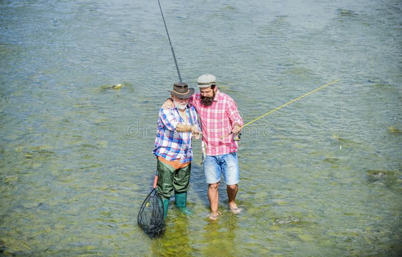 Coming together. male friendship. family bonding. summer weekend. mature men fisher. two happy fisherman with fishing. Rod and net. hobby and sport activity royalty free stock photos
