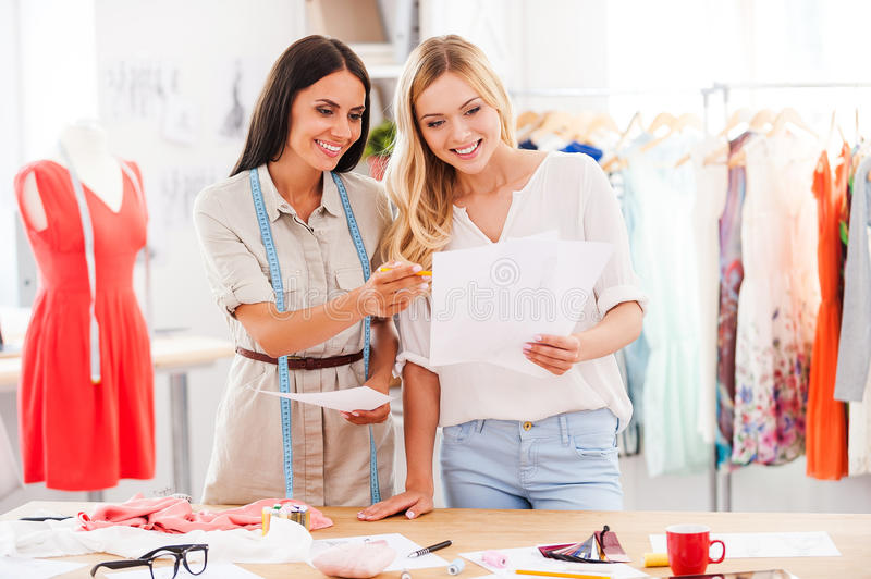 Coming up the new fashion styles. Two happy young women working together while standing in fashion workshop royalty free stock photo