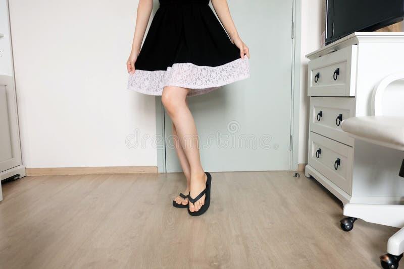 Comique femelle Femme dans la robe noire et des chaussures noires Une belle femme se tenant sur en bois dans le studio de chambre photo libre de droits