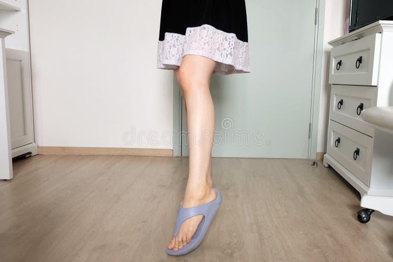 Comique femelle Femme dans la robe noire et des chaussures pourpres Une belle femme se tenant sur en bois dans le studio de chamb photo libre de droits