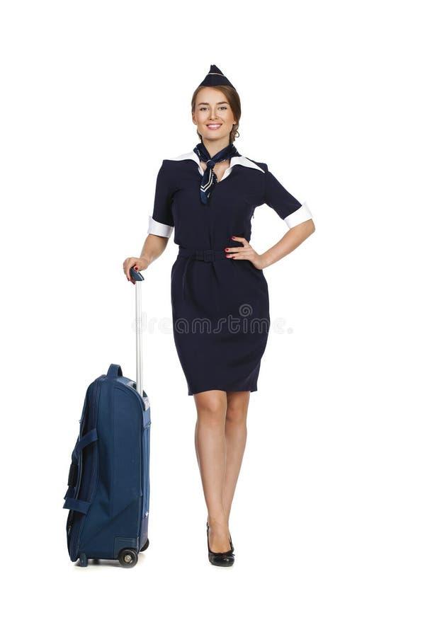 Comissária de bordo bonita que mantém a mala de viagem isolada no backgrou branco fotografia de stock