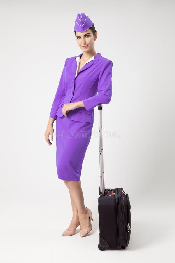 Comissária de bordo encantador Dressed In Violet Uniform And Suitcase foto de stock