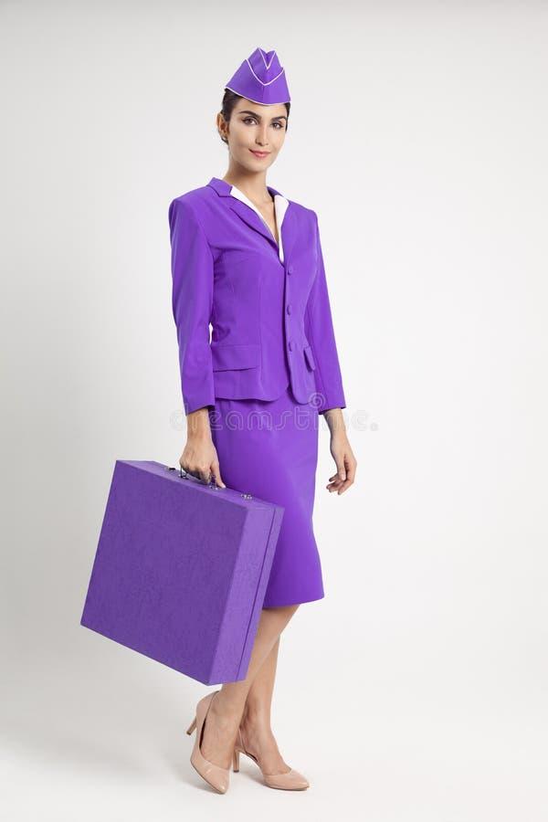 Comissária de bordo encantador Dressed In Violet Uniform And Suitcase imagem de stock