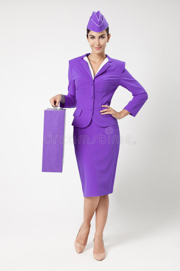 Comissária de bordo encantador Dressed In Violet Uniform And Suitcase imagem de stock royalty free