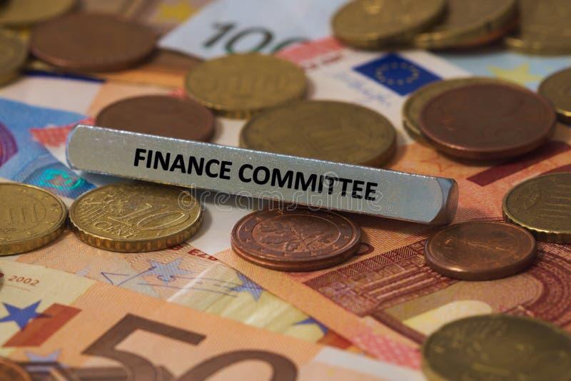Comitê das finanças - a palavra foi imprimida em uma barra de metal a barra de metal foi colocada em diversas cédulas fotos de stock