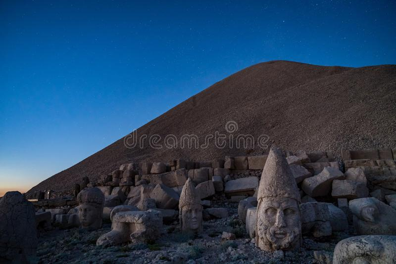 Commagene statues on the summit of Mount Nemrut during sunset with stars in the sky, Adiyaman, Turkey. Stone heads at the top of 2150 meters high Mount Nemrut royalty free stock image