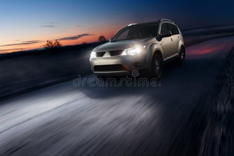 Commande de vitesse rapide de voiture sur la route goudronnée au crépuscule photographie stock libre de droits