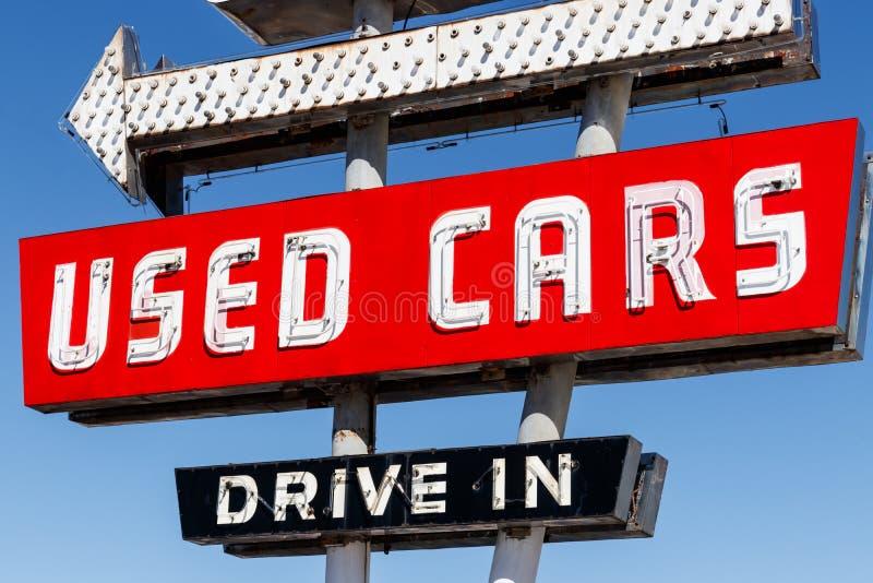 Commande de voiture d'occasion dans l'enseigne au néon des années 50 à un concessionnaire automobile pré possédé I photo libre de droits