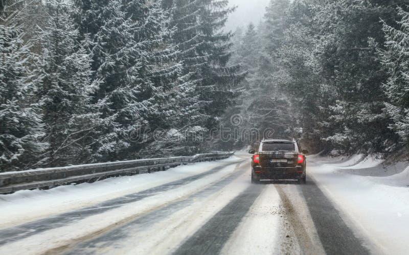 Commandes noires de voiture sur le chemin forestier couvert par neige pendant la tempête de neige, arbres des deux côtés, vue de  image libre de droits