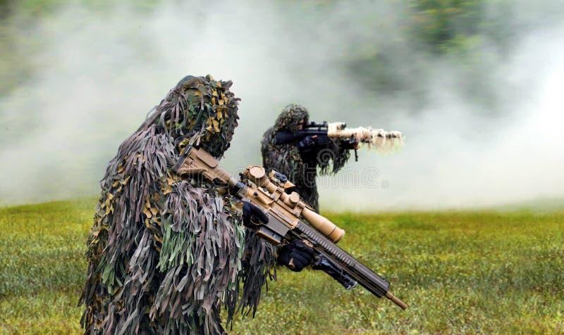 Commando vestito nel cammuffamento del ghillie durante la guerra di combattimento fotografie stock libere da diritti