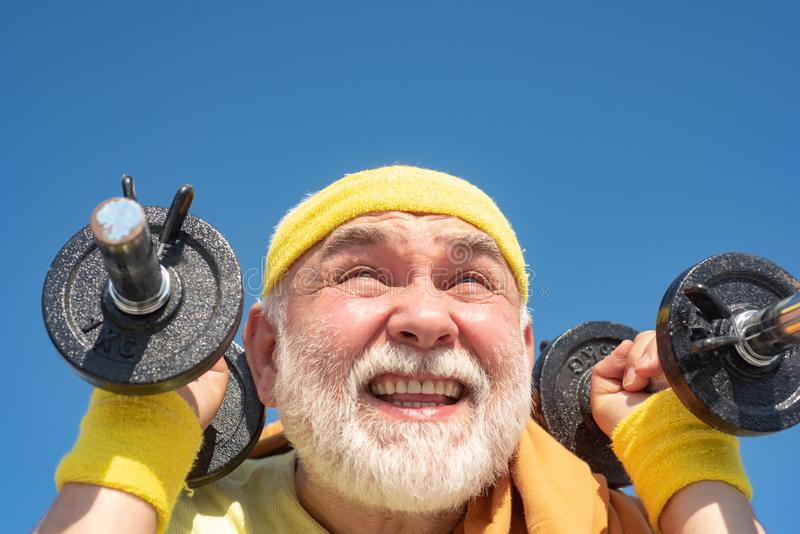 Comme des sports Concept sain de style de vie Sportman supérieur s'exerçant avec l'haltère de levage sur le fond de ciel bleu photographie stock