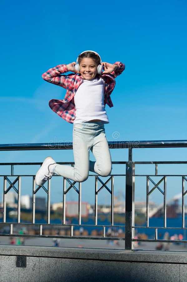 Comme une vedette du rock Peu fille sautant en musique Petit enfant heureux écoutant la musique Peu enfant appréciant la musique image libre de droits