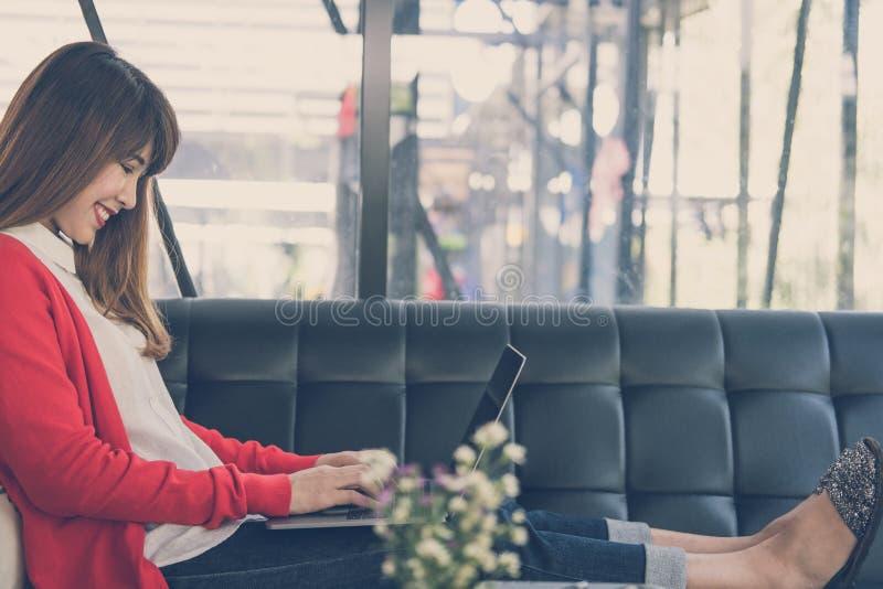commencez la femme dactylographier sur l'ordinateur tout en se reposant sur le sofa à la maison photo libre de droits