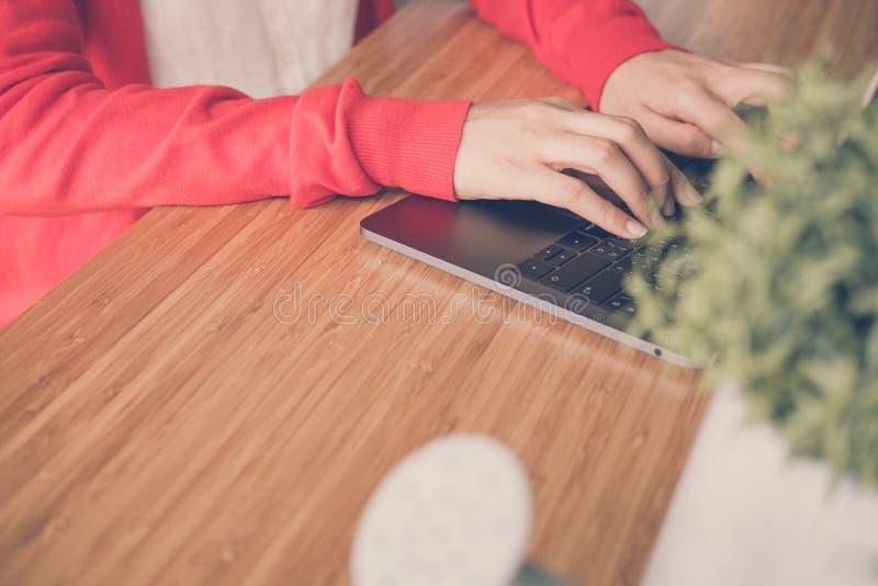 Commencez la femme porter le cardigan rouge dactylographiant sur l'ordinateur à la maison images libres de droits