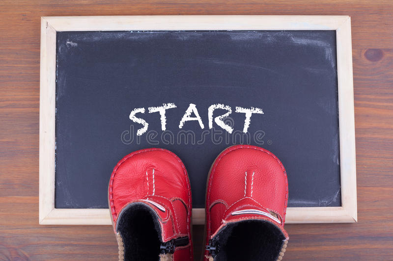 Commencez le message et badinez les chaussures dessus sur le tableau et le backgrou en bois image stock