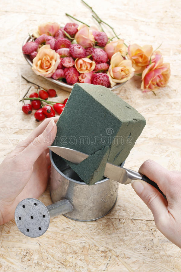 Comment faire l'arrangement floral dans la boîte d'arrosage de vintage image libre de droits