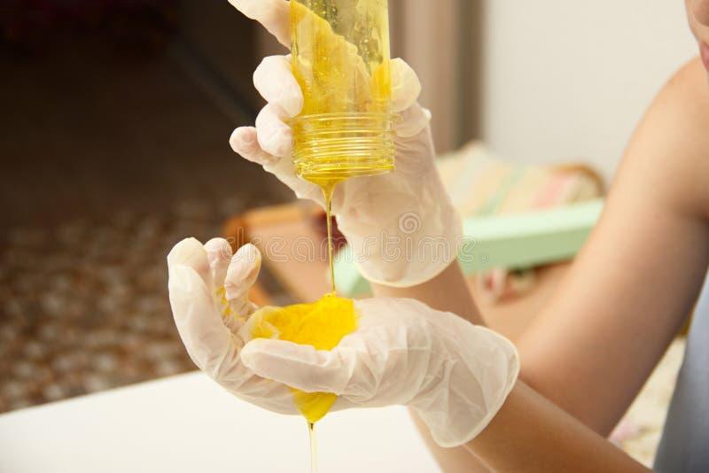 Comment faire la boue Une main femelle dans une boue faite maison de jaune de prises de gant protecteur est une fin de jouet du ` photographie stock