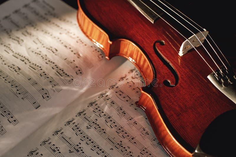 Comment lire le violon les notes se ferment vers le haut de la vue du violon en bois brun se trouvant sur la feuille avec des not photos libres de droits