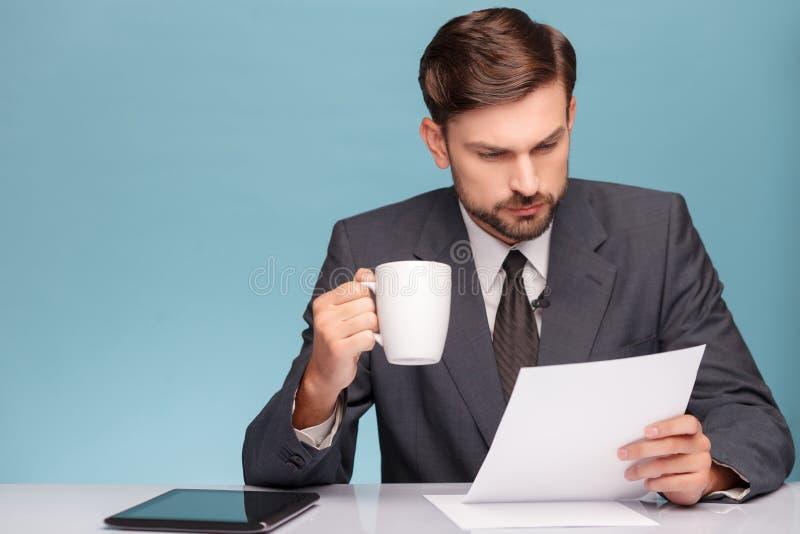 Commentatore del notiziario maschio attraente con la tazza di tè fotografia stock