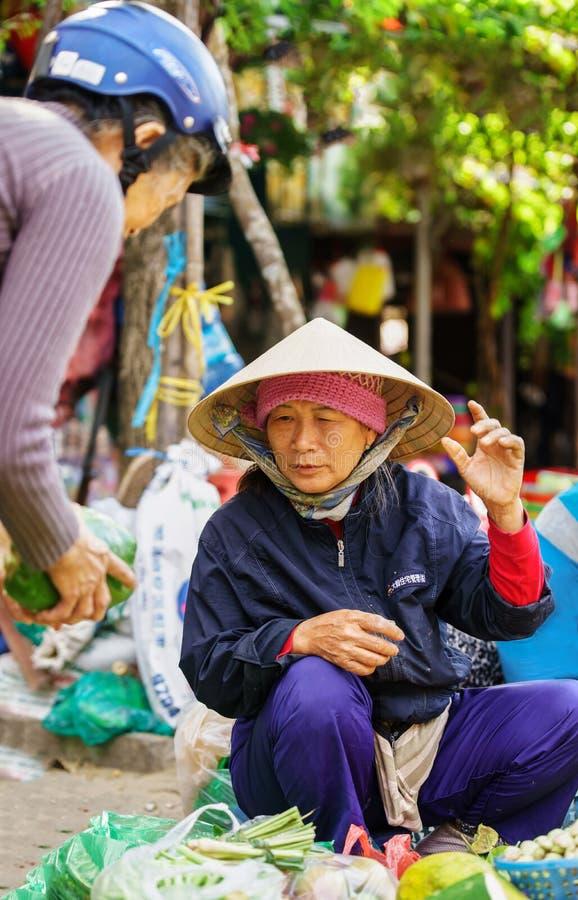 Commerçant asiatique dans le chapeau vietnamien traditionnel vendant le veg frais images stock