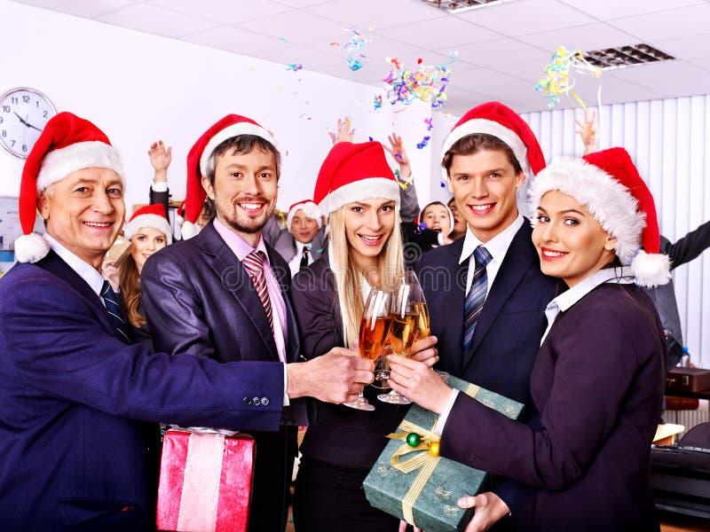 Commerciële groepsmensen in santahoed bij Kerstmispartij. stock foto's