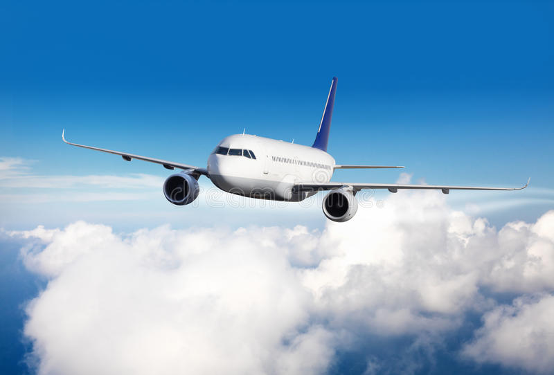 Commerciële jet die boven wolken vliegen stock afbeeldingen