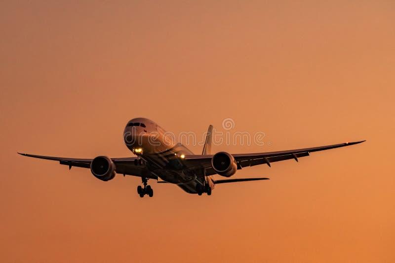 Commerciële luchtvaartlijn Passagiersvliegtuig die bij luchthaven met mooie zonsonderganghemel en wolken landen Aankomstvlucht Vl stock fotografie