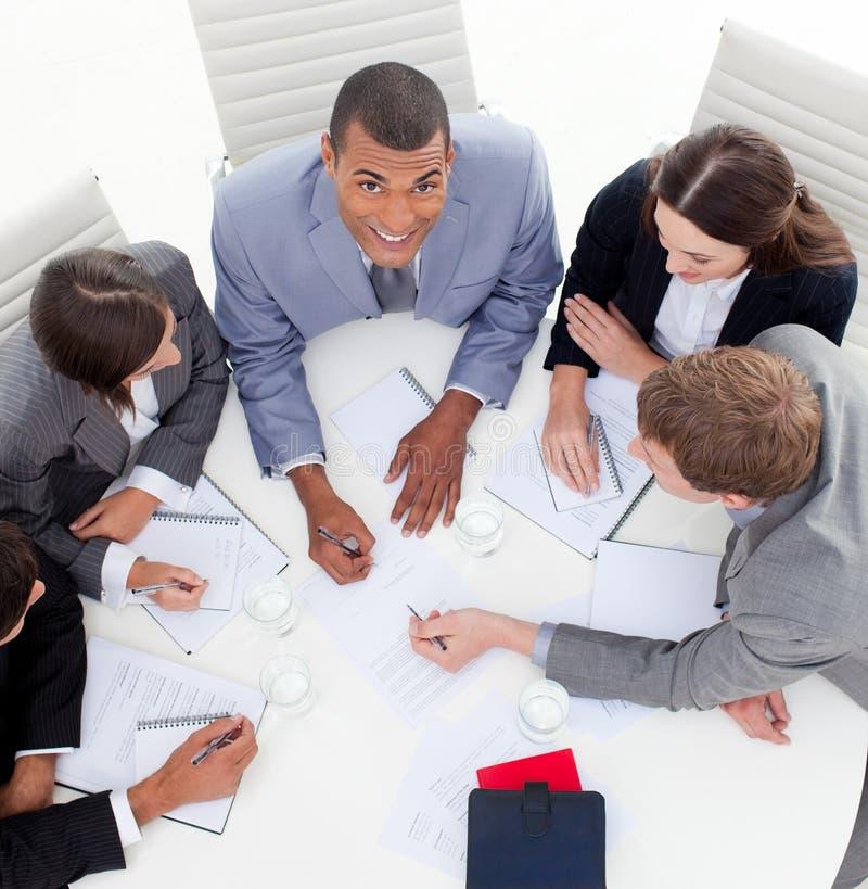 Commerciële teamzitting rond een conferentielijst royalty-vrije stock afbeelding