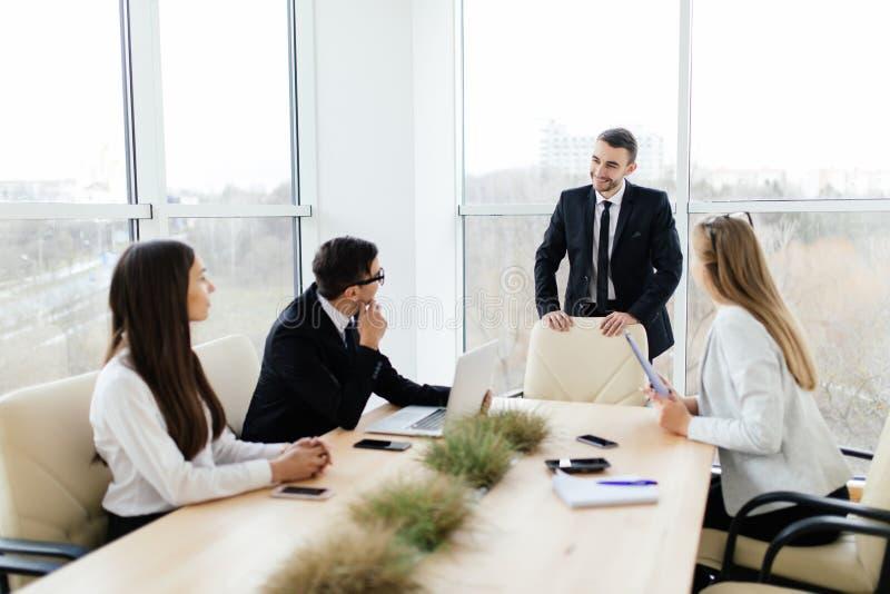 Commerciële vergadering Bedrijfsmensen in formalwear besprekend iets terwijl het zitten samen bij de lijst stock afbeeldingen