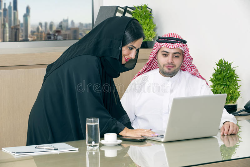 Commerciële Vergadering in bureau, Arabische zakenman & Arabische Secretaresse die hijab het werken aan laptop dragen royalty-vrije stock foto's