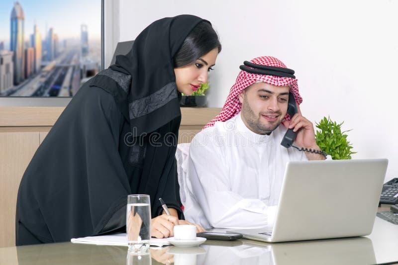 Commerciële Vergadering in bureau, Arabische zakenman & Arabische Secretaresse die hijab het werken aan laptop dragen stock afbeeldingen
