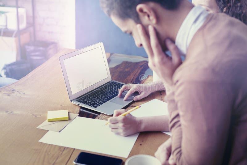 Commerciële vergadering in bureau, jonge ondernemer die, gebruikend laptop en lege bladen aan houten lijst samenwerken stock afbeeldingen