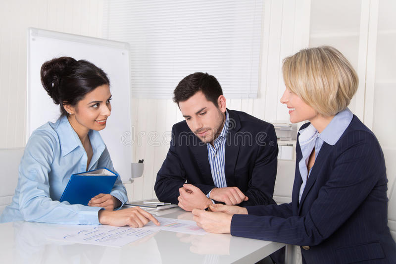 Commerciële vergadering Drie mensen die bij de lijst in een bureau zitten stock afbeelding