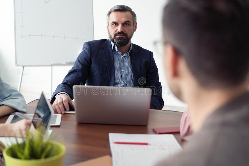 Commerciële vergadering Twee bedrijfsmensen die voor elkaar in het bureau zitten terwijl het bespreken van iets royalty-vrije stock foto's