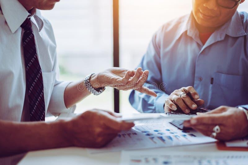 Commerciële vergaderings Aziatische mensen twee mannelijke midden-leeftijd die terwijl samen het zitten bespreken royalty-vrije stock afbeelding