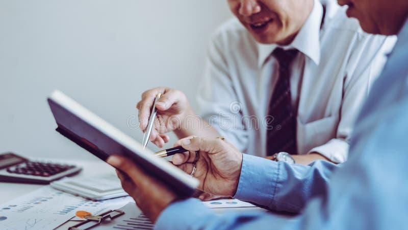 Commerciële vergaderings Aziatische mensen twee mannelijke midden-leeftijd die terwijl samen het zitten bespreken royalty-vrije stock foto's